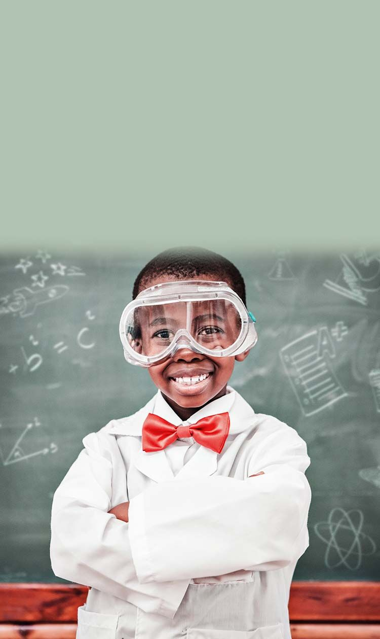 boy in labcoat and goggles having fun at an after school program
