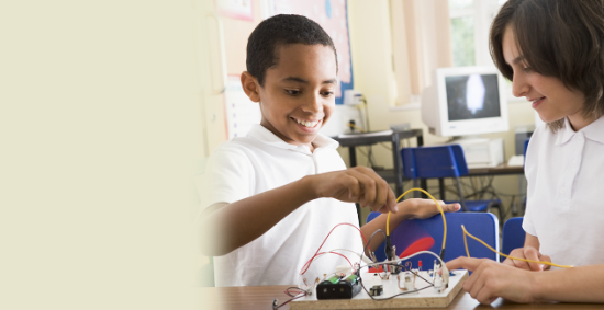 Boy and girl playing with wires attached to circuit board on a desk